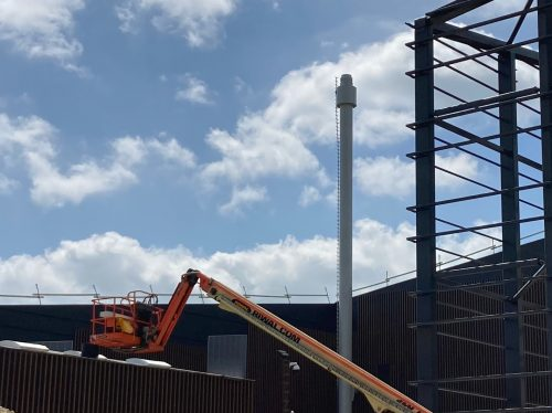 Smokestack with TMD. The TMD reduces VIV by increasing the Scruton number.   Smokestack TMDs are sometimes hidden inside the cylindrical stack, typical for large diameter multi-pipe stacks. Here, the TMD is in the annular chamber near the stack top.